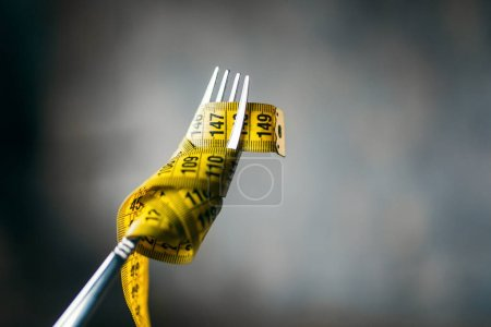 measuring tape on fork closeup, weight loss concept