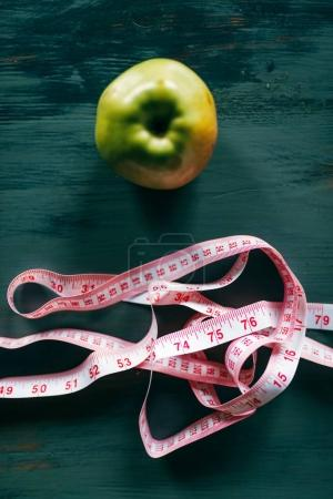 Photo for Apple and pink measuring tape on wooden table closeup, weight loss diet concept - Royalty Free Image