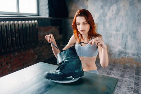 Photo for Unhappy skinny woman against plate with boot, absence of appetite - Royalty Free Image