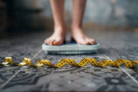 female feet on scales closeup, measuring tape, weight loss, hard dieting