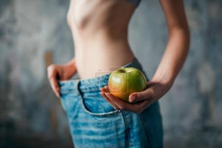 woman with apple in hand tries on big size jeans, weight loss