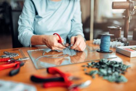 woman holding pliers, master at workplace, handmade jewelry, needlework, fashion bijouterie making