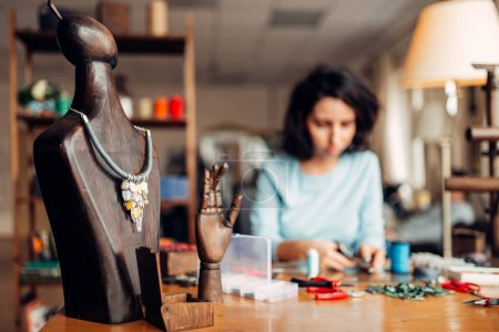 handmade necklace on wooden mannequin, needlework, female craftsman at workplace on background