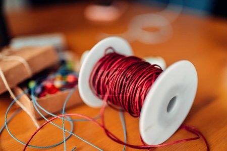 Photo pour Travaux d'aiguille, bobine avec une corde décorative rouge, accessoires faits à la main - image libre de droit