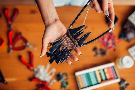 female hand handmade necklace, needlework, female craftsman at workplace