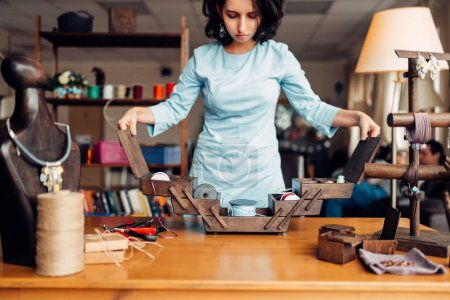 needlework tools and equipment, female master at workplace in workshop
