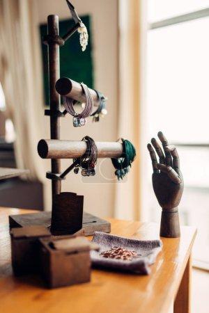 needlework accessories, bracelets and wooden hand in workshop