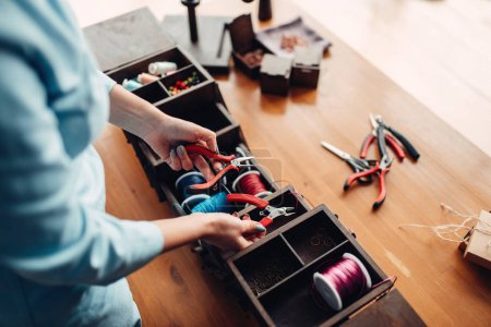 Photo for Needlework tools and equipment, female master at workplace in workshop - Royalty Free Image