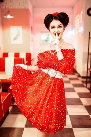 Photo pour Glamour pin-up heureuse femme en robe rouge posant dans café rétro intérieur - image libre de droit