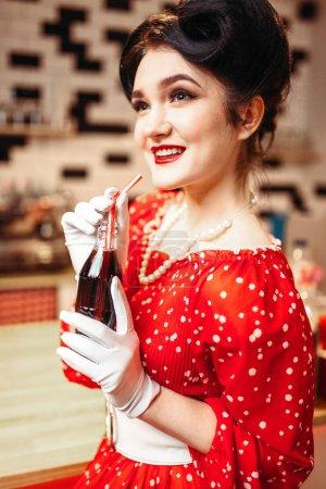 Photo pour Pinup femme buvant gazéifiées boisson au café rétro, rouge robe à pois, style vintage - image libre de droit