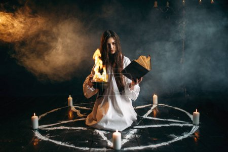 young woman in white shirt sitting in the center of pentagram circle with candles and reading a spell, dark magic ritual, occultism