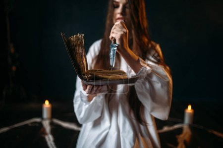 witch in white shirt holding knife and reading spell, pentagram circle with candles, black magic ritual process