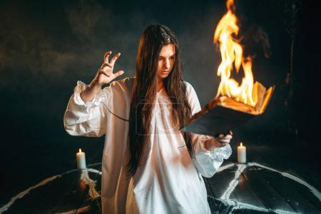 Witch in white shirt  reading spell, pentagram circle with candles, dark magic ritual. Occultism and exorcism