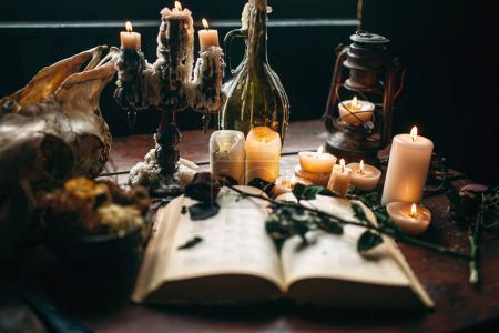 witchcraft, black magic, candles with ritual book on table, occult and esoteric symbols
