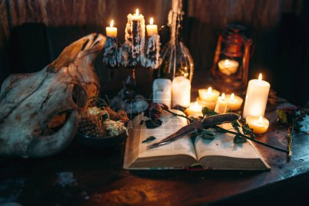 witchcraft, dark magic, candles with ritual book on table,occult and esoteric symbols