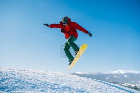 Photo pour Snowboarder de sauter sur la pente vitesse, sportif en action, active sport d'hiver, mode de vie extrême - image libre de droit