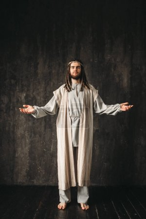 Jesus Christ with open arms, dark background, Christian faith, son of God