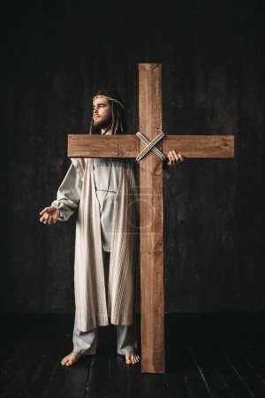 Photo for Crucifixion of Jesus Christ, symbol of christian religion. Man with cross on black background. The great martyr - Royalty Free Image