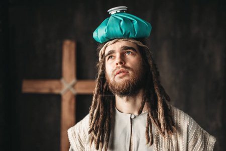 Jesus Christ with heating pad on head, crucifixion cross on black background