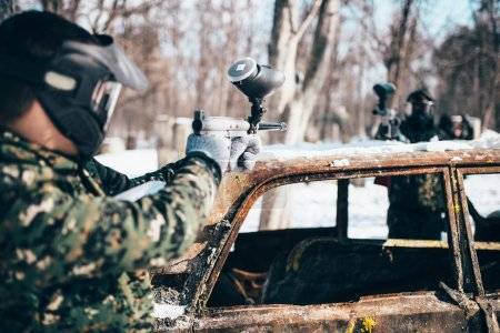 paintball battle, players fight around burned car in winter forest