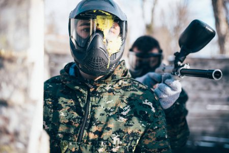 two paintball players in military uniform and masks, winter battle