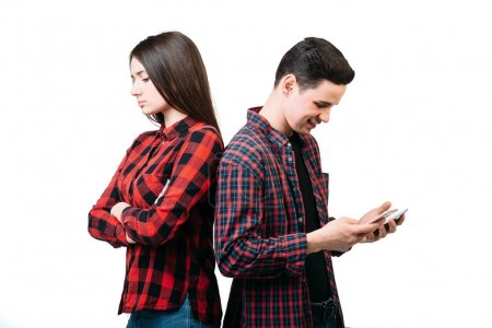 Smartphone addicted people. Couple standing back to back, man using mobile phone, white background. Manipulation of consciousness concept