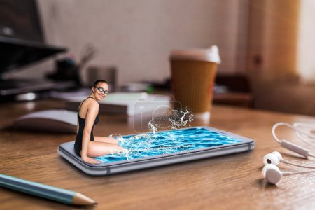 Photo for Female swimmer sits on the edge of large phone screen with water, table with big coffee cup on background. Mobile and communication technology addiction, social addicted people. Scaling effect - Royalty Free Image