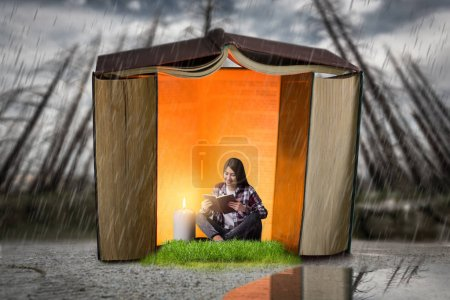 Woman reads in a house built of books, scale effect. Reading concept, small man in a big world of knowledge
