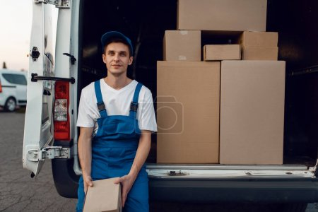 Photo for Deliveryman in uniform gives parcel to female buyer at the car, delivery service, delivering. Man holding cardboard package near the vehicle, male deliver and woman, courier or shipping job - Royalty Free Image