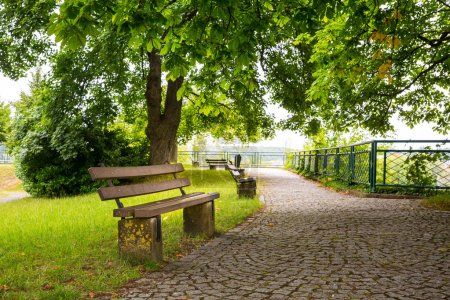 Benches in green park, old European town, nobody. Summer tourism and travels, famous europe landmark, popular places for tourists