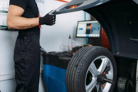 Photo pour Fixation mécanique roue cassée sur la machine d'équilibrage, service des pneus. Homme répare pneu de voiture dans le garage, voiture sur prise d'ascenseur, inspection dans l'atelier - image libre de droit