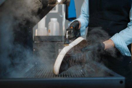 Photo pour Shoemaker traite les chaussures sur une machine spéciale, service de réparation de chaussures. Compétence d'artisan, atelier de cordonnerie, travaux de maître avec des bottes - image libre de droit
