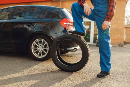 Photo for Male worker in uniform poses with tyre, tire service. Vehicle repair service or business, man change wheels on automobile outdoor - Royalty Free Image