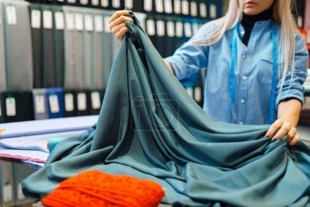 Photo pour Seamstress travaille en atelier textile. La femme tient le tissu à coudre, la couture féminine sur le lieu de travail, la couture - image libre de droit