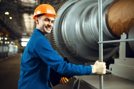 Photo for Male engineer on factory, large turbine on background, plant. Industrial production, metalwork engineering, power machines manufacturing - Royalty Free Image