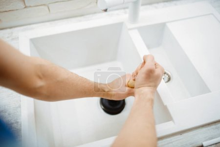 Male plumber in uniform holds plunger, problem with clog in the kitchen. Handyman with toolbag repair sink, sanitary equipment service at home