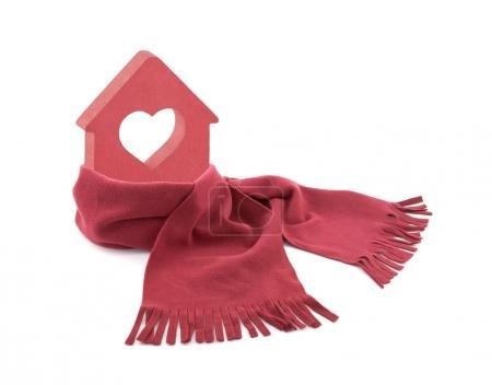 Foto de Pequeña casa roja con corazón envuelto en una bufanda aislada en blanco - Imagen libre de derechos