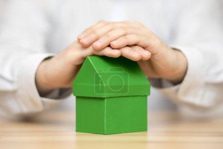 Photo pour Petite maison verte, protégée par des mains - image libre de droit
