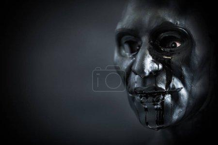 Photo pour Figurine effrayante avec masque sanguinaire effrayant dans le noir - image libre de droit