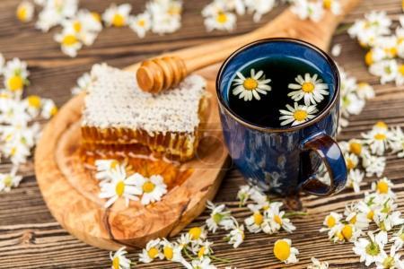 Photo pour Thé nid d'abeille et camomille sur table en bois - image libre de droit