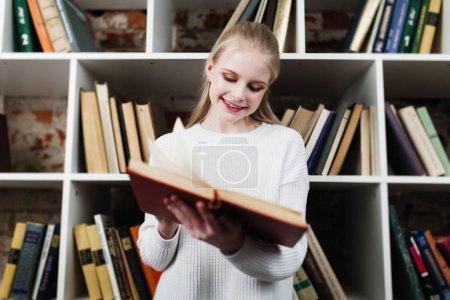 Photo pour Adolescente lisant un livre à la bibliothèque - image libre de droit