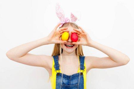Photo pour Adolescente, portant des oreilles de lapin tenant des oeufs de Pâques - image libre de droit