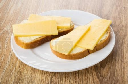 Sandwiches with butter and cheese in plate on table