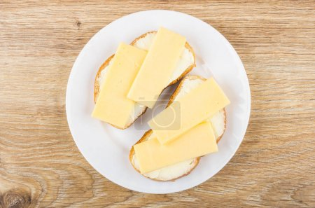 Sandwiches with butter and cheese in white plate on table
