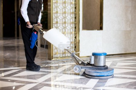 man polishing marble floor in office