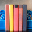 Colorful books on table in modern study...