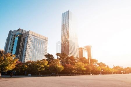 Photo pour Immeubles de bureaux modernes de basket vide dans le ciel ensoleillé - image libre de droit