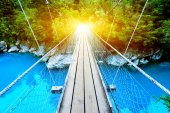 footbridge over clean water with sunbeam in forest