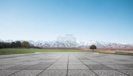 empty brick floor with snow mountains