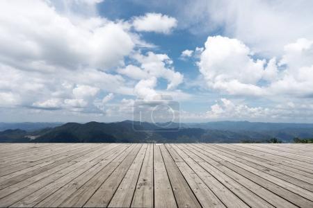 empty wooden floor with green hill in cloud sky